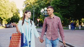走穿过有购物袋的城市的年轻夫妇 T 股票录像