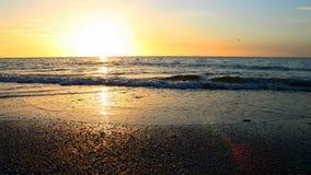 走路在海洋的日落光芒 库存照片