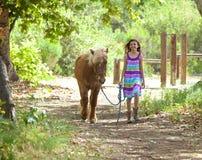 走逗人喜爱的小女孩她的小马 库存照片