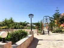 走通过一个公开热带庭院的妇女 图库摄影