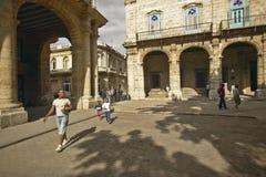 走通过一个老广场的古巴妇女和孩子在哈瓦那旧城,有拱道的古巴 免版税库存图片