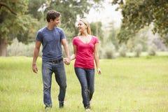 走通过乡下的浪漫年轻夫妇 免版税库存照片