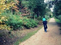 走通过公园的父亲和孩子 图库摄影