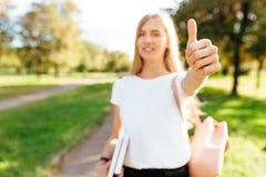 走通过公园的美丽的男女共学女孩拿着书他 免版税图库摄影