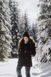 走通过冷淡的风景冬天森林的女孩 免版税库存图片