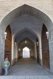 走通过半球形的义卖市场的拱道的妇女在布哈拉,乌兹别克斯坦 免版税库存图片