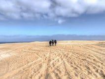 走通过含沙地形的三个人 免版税图库摄影