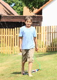走通过喷水隆头的男孩 免版税库存照片
