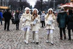 走通过圣诞节市场的三个天使在柏林 库存照片