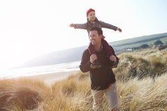 走通过在冬天海滩的沙丘的父亲和女儿 免版税库存图片