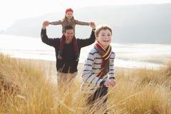 走通过在冬天海滩的沙丘的父亲和孩子 库存照片