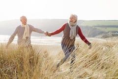 走通过在冬天海滩的沙丘的资深夫妇 库存照片