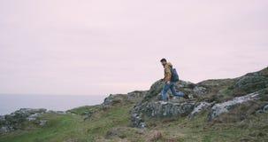 走通过大峭壁年轻人游人,在莫赫悬崖上面的令人惊讶的地方到达了  股票录像