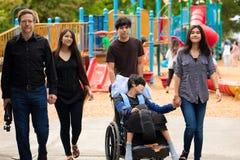 走通过有残疾儿子的操场的家庭轮椅的 库存照片