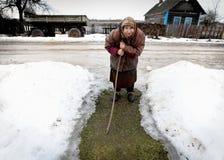走通过村庄的老妇人 免版税库存照片