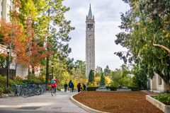 走通过校园的学生和访客在一晴朗的秋天天; 库存照片