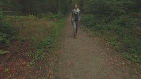 走通过森林的一个少妇的天线,然后向后ascenting在她的低空接近的跟踪的射击 影视素材