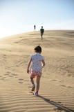 走通过沙漠的女孩跟随她的家庭 免版税图库摄影