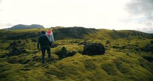 走通过熔岩荒野的夫妇鸟瞰图在冰岛 男人和妇女坐岩石,享受风景 股票录像