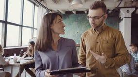 走通过现代办公室和谈的两个同事 白种人谈论男人和亚裔的妇女本文 股票录像