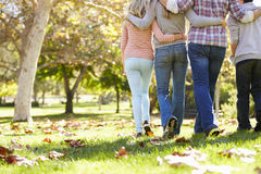 走通过秋天森林地的家庭背面图 库存照片
