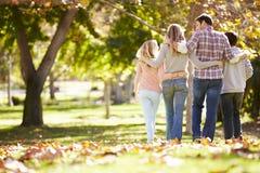 走通过秋天森林地的家庭 库存照片