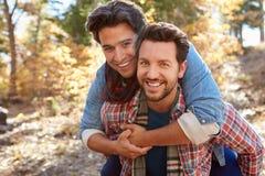 走通过秋天森林地的快乐男性夫妇画象  库存图片