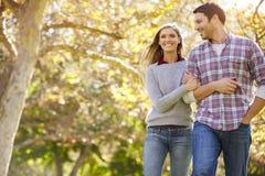 走通过秋天森林地的浪漫夫妇 库存图片