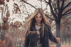 走通过秋天森林的摇摆物女孩 库存照片