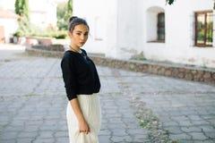 走通过老镇的街道的年轻美丽的妇女 库存图片