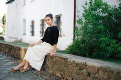 走通过老镇的街道的年轻美丽的妇女 库存照片