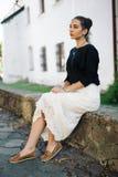 走通过老镇的街道的年轻美丽的妇女 图库摄影