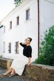 走通过老镇的街道的年轻美丽的妇女 免版税库存图片