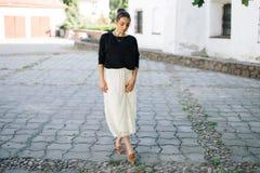 走通过老镇的街道的年轻美丽的妇女 免版税库存照片