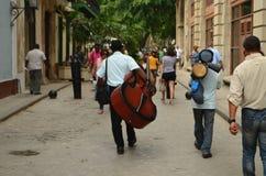 走通过老Havanna的低音提琴球员 免版税库存图片