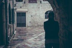 走通过街道黑暗的隧道的偏僻的妇女剪影在雨天在老城市在与拷贝空间的雨期间 免版税库存图片