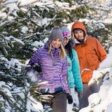 走通过雪冬天森林的朋友 免版税库存图片