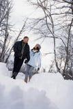 走通过雪的成熟夫妇 库存图片