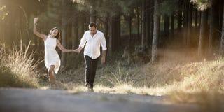 走通过领域的年轻英俊的印地安夫妇 免版税库存照片