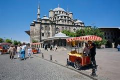 走通过17世纪清真寺的快餐摊位和游人在伊斯坦布尔 图库摄影