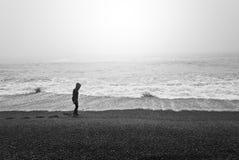 走通过黑沙子冰岛海滩在一有雾的天 免版税图库摄影