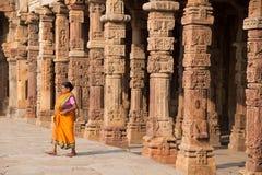走通过Quwwat Ul回教清真寺庭院的印地安妇女  库存图片