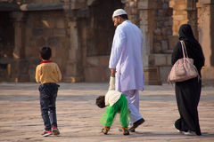走通过Quwwat Ul回教mosqu庭院的印地安家庭  库存照片
