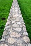 走道由岩石和混凝土制成在绿色草坪 库存图片