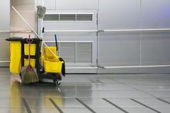 走道的黄色清洁台车公园在不锈的墙壁backgr 免版税库存照片