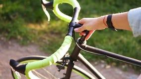 走除一辆自行车以外的一个少妇的瞄准的顶视图英尺长度在早晨公园或草坪 走与她的女孩 股票录像