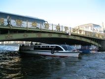 走,观光的小船,漂浮在桥梁下,在涅瓦河 免版税库存照片