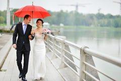走他们的婚礼之日的年轻婚礼夫妇 免版税库存图片