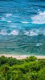走Nunggalan海滩的人 滚动大的波浪  Uluwatu,巴厘岛,印度尼西亚 免版税库存图片