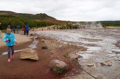 走Strokkur Geysir的未认出的女孩在冰岛 免版税图库摄影